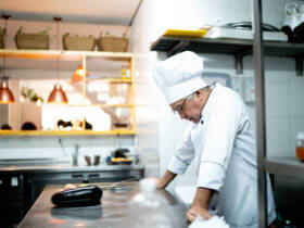 A worried senior chef in the kitchen counter